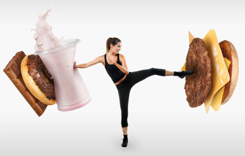 fit-young-woman-fighting-off-fast-food